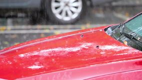 Rain water drops falling on red car in parking lot, slow motion in 180 fps, heavy rain fall background.  stock video footage
