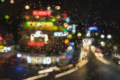 Rain water drops on a window glass after the rain with cityscape and street view on background.  Stock Photos