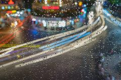 Rain water drops on a window glass after the rain with cityscape and street view on background.  Stock Photo