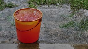 Rain water falling from the roof into the red bucket stock video footage
