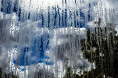 Glass window with rain, sky clouds and sun on background stock photos