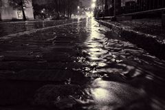 Rain water flowing on a cobblestone street in Helsinki Stock Photos