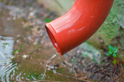Rain water flowing from drain pipe. Closeup Royalty Free Stock Photography