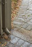 Rain water leak from a gutter onto the ground royalty free stock photos