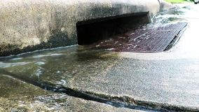 Rain water running into a storm drain stock video