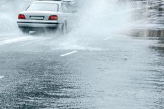 Rain water splashing from wheels of car in motion. Rainy weather in autumn royalty free stock photos