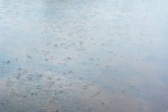 Rain on water surface. Royalty Free Stock Photography