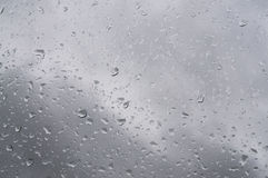 Rain waterdrops on glass surface against gray sky Stock Images