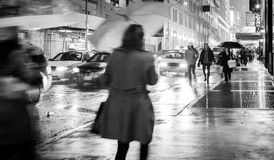 Rain on wet city street. At night, people with umbrellas. Manhattan, America stock photography