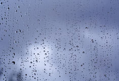 Rain on the window. Raindrops on glass, dark cloudy skies in the background. Reflections of trees in the raindrops royalty free stock photo