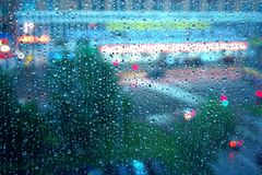 Rain window. View on a city street through window glass covered by rain drops Stock Photos