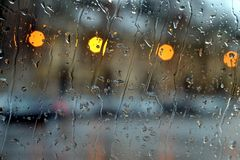 Rain on window with blurred background stock photos