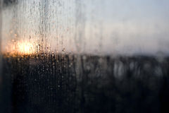 Rain on Window. Rain on a window with the sun rising in the background Royalty Free Stock Images