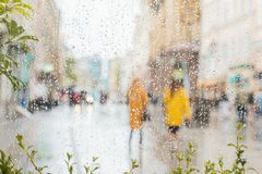 Rain on a window, looking out to people in a street scene. Silhouettes of girls in bright beautiful yellow coats. Rain on a window, looking out to people in a Royalty Free Stock Images