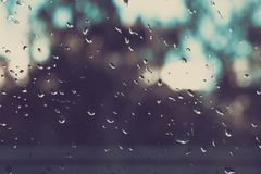 Rain on a Window. Rain on a window blurs the outside to an out of focus pattern. Drops on the glass. rain on glass. Rain on a Window. Rain on a window blurs the Royalty Free Stock Images