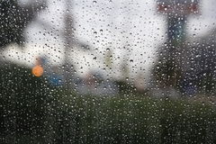 Rain on The Window. While it rains in Thailand shooting through a window saw a beautiful raindrops Royalty Free Stock Image