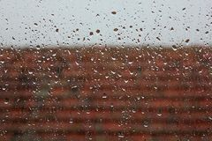Rain from window with roof. Drops of rain on window glass with wet roof stock images