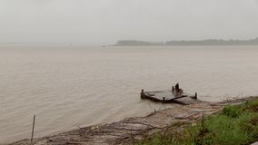 Rain , winds ,  mekong,  cambodia. Person waiting ferry boat under rain at landing stage. Mekong, Cambodia stock footage