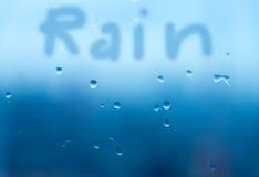 Rain writing on raindrop on wet mirror. Mirror with rain drop background in blue tone with hand writing 'Rain Stock Photos