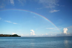 Rainbow. Wide shot of rainbow across the ocean along Tumon Bay in tropical island of Guam Stock Images
