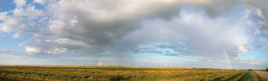 Rainbow. The solar rain pours over a field, there was a rainbow which was stretched over huge open space Stock Image