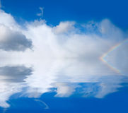 Rainbow. On a background of clouds and water stock illustration
