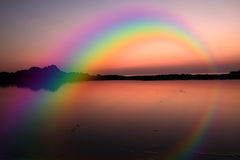 Rainbow. At pink sunset sea Stock Image