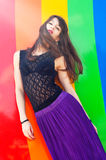 Rainbow. Pretty young brunette woman wearing black lace top and purple skirt with wind in her long hair against rainbow color background Stock Image