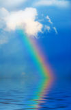 Rainbow. In the sky during rain on blue stock photos