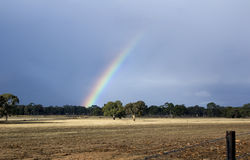 Rainbow. Over field with approaching storm Stock Images