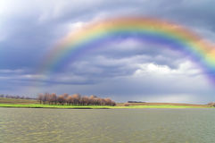 Rainbow. Above lake after a rain stock photography