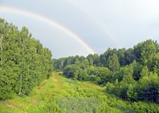 Rainbow. Twofold rainbow over green birch forest Stock Photo