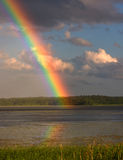 Rainbow. Over a lake, reflected in the water Royalty Free Stock Photo