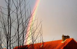 Rainbow above a house, bare branches in winter. Sunset Stock Photography