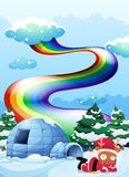 A rainbow above the igloo beside the reindeer Royalty Free Stock Photo