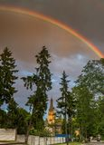 Rainbow above Lutheran church in Dubulti, Jurmala, Latvia. The church was built in 1909 with traits of asymmetry and national Latvian romanticism style Stock Image