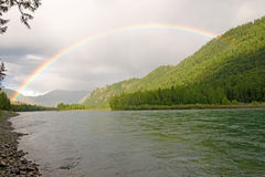 Rainbow above river. In mountains Royalty Free Stock Photos