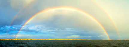 Rainbow above river Stock Images