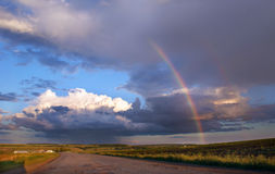 Rainbow above road. Clouds and rainbow above road Stock Photos