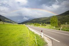 Rainbow above road and mountains Stock Photos
