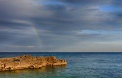 Rainbow above rocky coast on peninsula Kamenjak in Croatia Royalty Free Stock Image