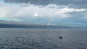 Rainbow above small fishing boat in thunderstorm. Storm clouds above shore, solitude at sea, fisherman, unrecognizable in small vessel, Adriatic sea, Croatia stock video footage