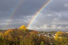 Rainbow above the village in autumn Royalty Free Stock Photography