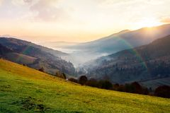 Rainbow above the village in foggy valley. Beautiful mountainous countryside at sunrise in autumn royalty free stock photos
