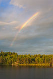 Rainbow above wood lake Stock Photo