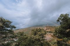 Rainbow against the sky and mountains with a pine forest. stock photos