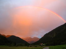 Rainbow over alpenglow mountain scenery Stock Image