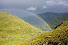 Rainbow in the Alps. Rainbow over Oberalppass, Alpine pass in cantons Graubuenden and Uri in Switzerland Royalty Free Stock Image