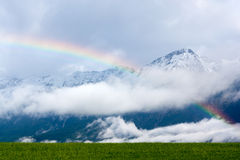 Rainbow in the Alps. Rainbow over a green meadow in the Alps, with snowcapped hills in the background Royalty Free Stock Images