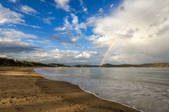 Rainbow over ocean and beach against cloudy sky. Rainbow appearing against cloudy blue sky over Ocean Beach at Umina, Australia after storm stock images